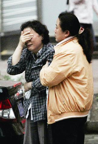 小陈的母亲在家人搀扶下哭着离开现场