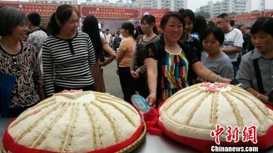 图为两位包子师傅展示一个60斤重的大包子,引来市民围观。 邹海斌 摄