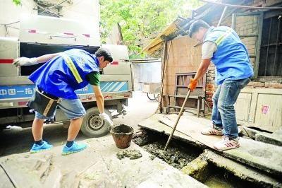 """五福路一老社区里,""""80后""""的王轩在疏捞堵塞的粪池。记者 苗剑摄"""