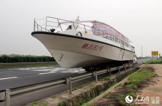 一辆装载游艇的半挂车行驶在高速公路